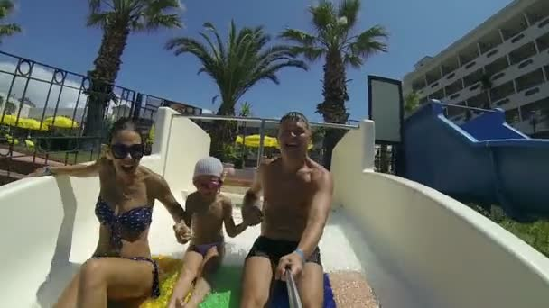 Mom dad and daughter go down the water slide.