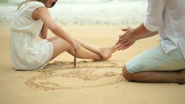Fiatal szerelmespár felhívni a szív formák a homok a tengerparton.