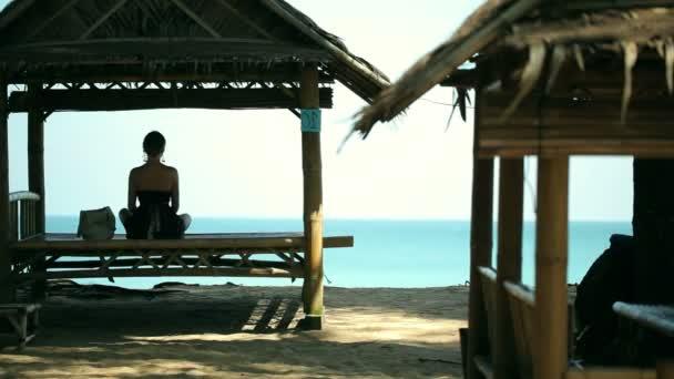 Silhouette junge Frau übt Yoga im Pavillon vor dem Strand.
