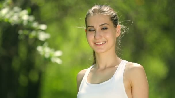 Attractive young woman dressed in white topic smiling at the camera in the park. Portrait of sporty girl.