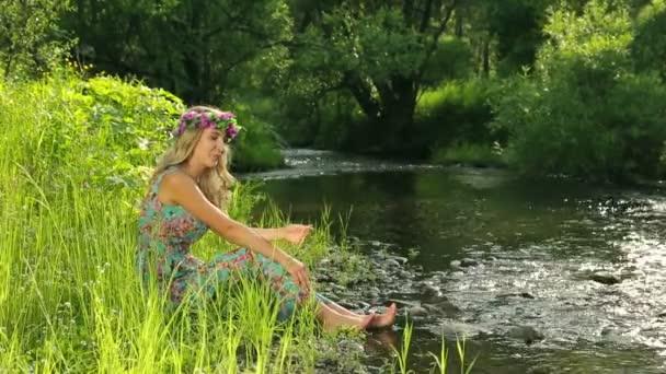 Mladá krásná žena květinový věnec u řeky. Krásná dívka, sedící u řeky.