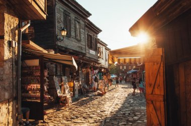 People walk through streets of ancient nesebar at sunset.