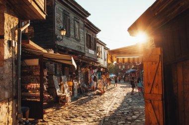 People walk through streets of ancient nesebar at sunset.