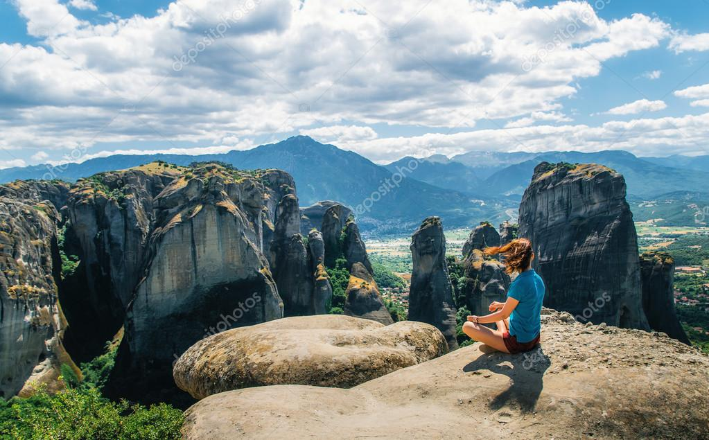 Girl sitting on the view point of the mountain. Traveler enjoying the mountain landscape of Meteora, Greece