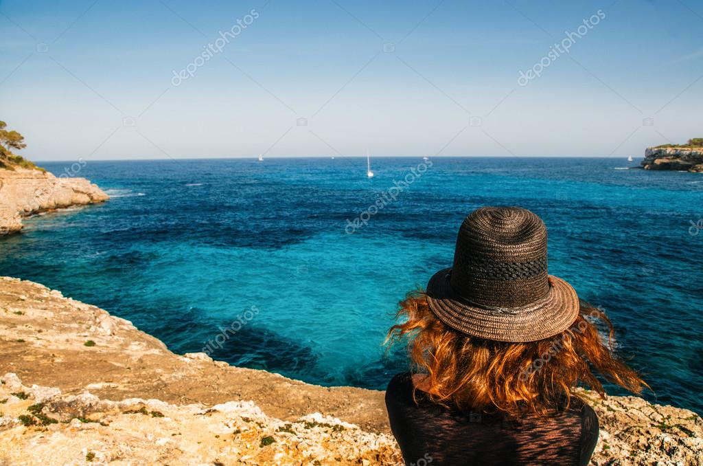 Girl in a hat looks at the azure water in the Bay of Mondrago Park. Traveler enjoying the seascape Mallorca, Spain