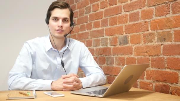 Usmívající se asistent pomocí sluchátek s mikrofonem v call centru, online služby zákazníkům