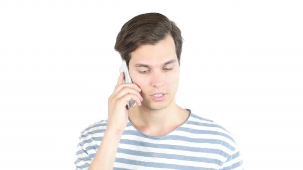 Vonzó fiatal ember nevetve beszél telefonon, elszigetelt fehér háttér