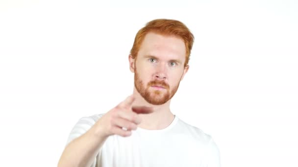Smiling redhair young man pointing finger at camera , white background