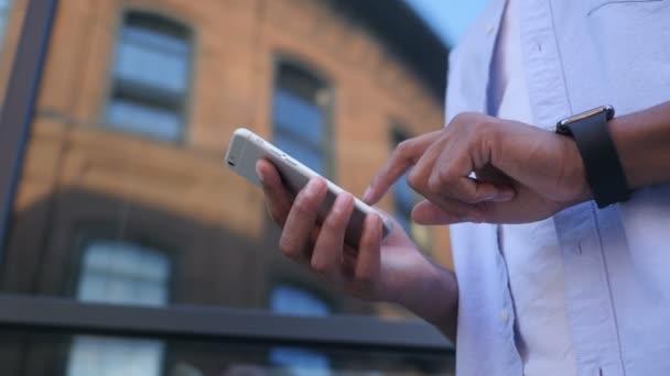 SMS, SMS auf dem Smartphone, junge schwarze Designer im Stehen