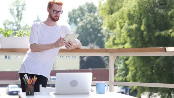 Zaneprázdněný prací na tabletu, procházení, stojící v balkon funkční venkovní, gesto