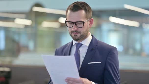 Porträt eines Geschäftsmannes mittleren Alters beim Lesen von Dokumenten