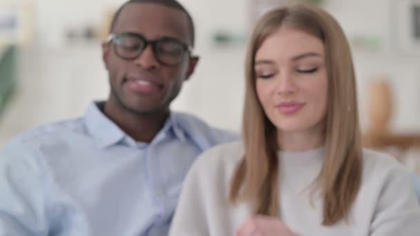 Attraktives gemischtes Rassenpaar, das in Herzform die Hände zusammenhält