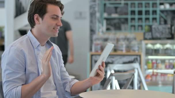 Junger Mann telefoniert mit Tablet in Café