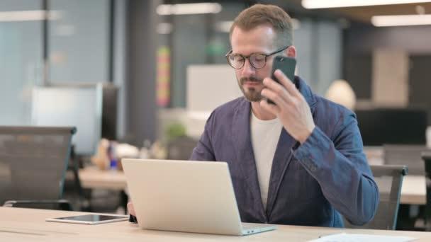 Středověký podnikatel Mluvení na smartphonu při použití notebooku