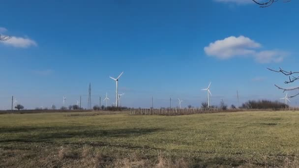 Pan left long shot wind farm renewable energy green yellow grass trees blue sky