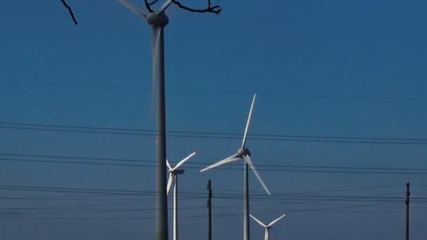 Slow motion wind turbines eco renewable energy blue sky white clouds power lines