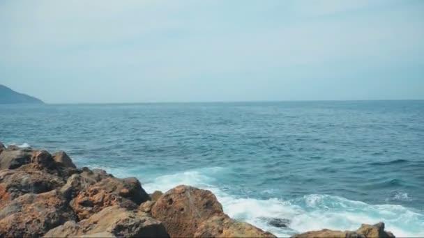 Klidné moře modré vody, vlny narážely do skal
