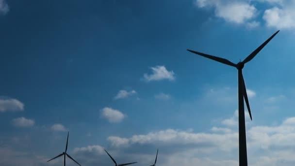 Větrné turbíny na modrou oblohu s bílé mraky vyrábějící ekologicky čistou energii