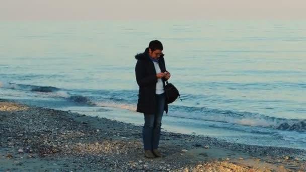 Žena v modrých džínách sběr oblázky na pláži