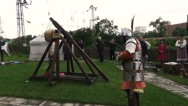 Medieval knight in full shining armory with helmet and steel sword fires old wooden trebuchet catapult towards fortified castle wall