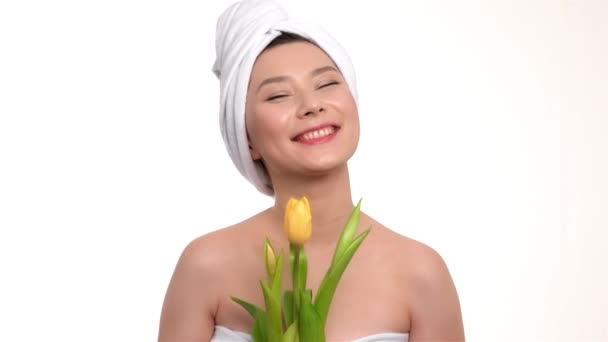 Happy girl with a towel on head holds yellow tulips
