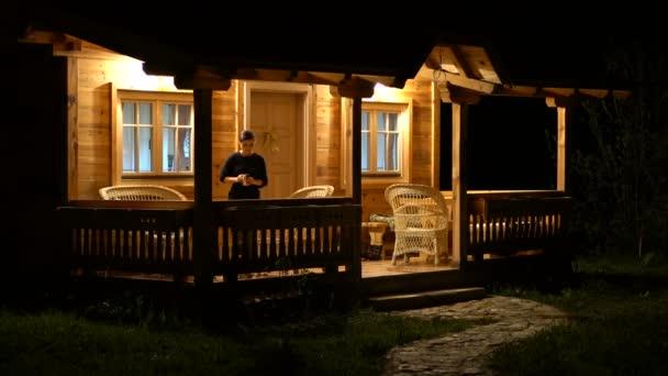 Mladá žena odpočívá na verandě a pití kávy v noci