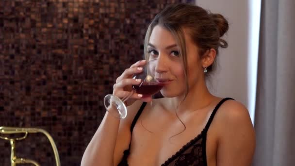 beautiful sexy girl with a glass of wine in bathroom