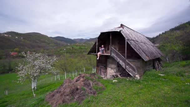 Žena sedí na balkóně dřevěného domu, zelené údolí