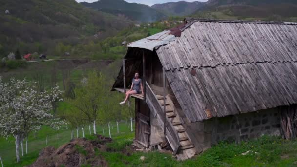 Asijská žena sedí na balkóně dřevěného domu, zelené údolí