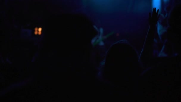 people waving hands at live concert, strob light