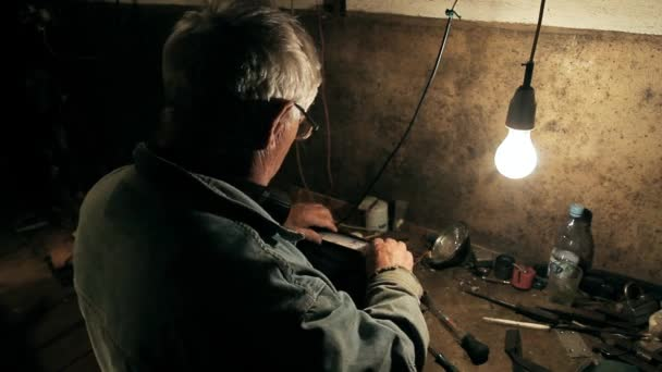 Egy régi szerelő dolgozik a garázsában