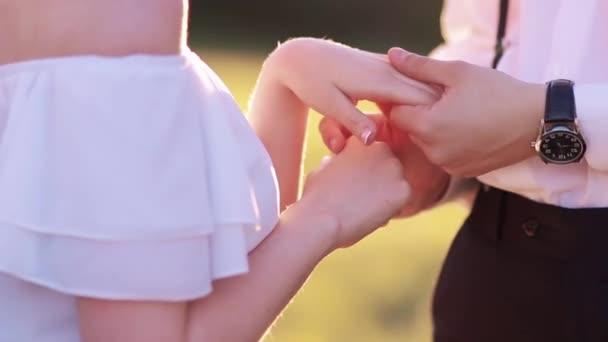 Mani della sposa e dello sposo al tramonto