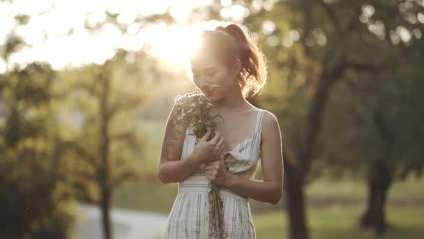 Boldog fiatal lány szagolgatja a virágokat, élvezi a természetet és mosolyog. Portré egy nőről, aki a napfény előtt tölti a hétvégét vagy vakációt a szabadban. Gyönyörű nő kamillákkal a kezében pihen a parkban..