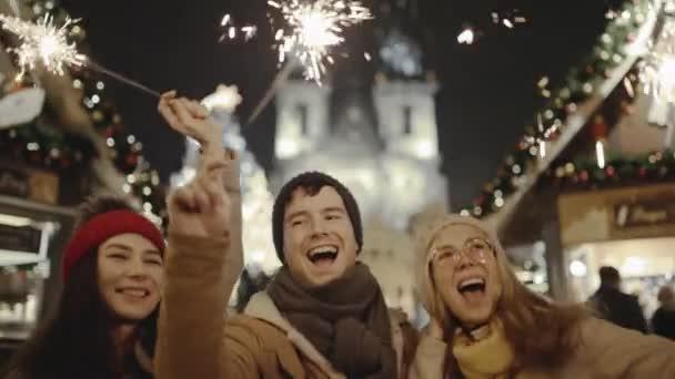 Csinos fiatal barátok nevetnek és táncolnak csillagszórókkal az utcán. Mosolygó emberek sétálnak az ünnepi vásáron szilveszterkor New Yorkban. Boldognak lenni együtt és valóra váltani az álmokat..