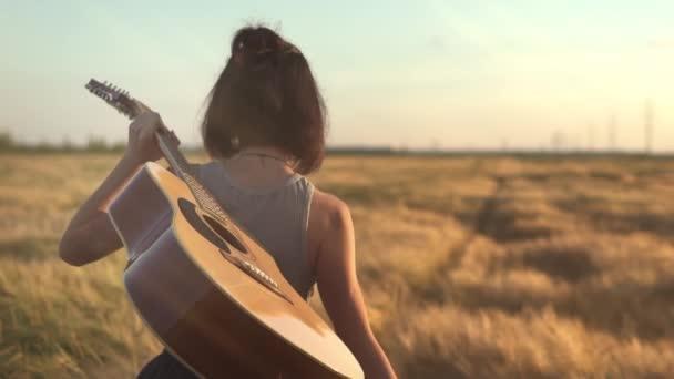 Detailní záběr Mladý hipster dívka drží kytaru v ruce a chodí v pšeničném poli. Žena s akustickým nástrojem užívající si přírody a slunečního světla. Lidé, životní styl, student, výraz a styl koncepce