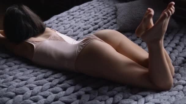 Felnőtt tartalom. Divatos gyönyörű női csábító modell meztelen fehérneműben pihentető ágyban és flörtölés. Szexi ázsiai nő szexi fehérneműben pózol a hálószobában a kamerának. Glamour erotikus koncepció.
