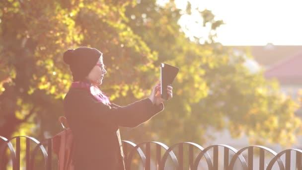 Glückliche Touristen im Urlaub. Hübsches junges Mädchen beim Fotografieren des Sonnenuntergangs. Touristinnen spazieren durch die Stadt. schön sinlight glänzend.