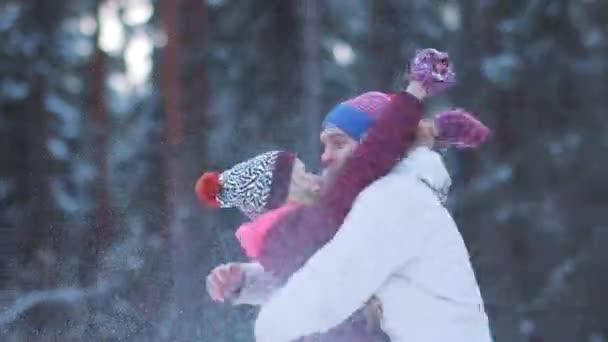 Mladí milenci objímat a hrát sníh v zimním lese pozadí. Mladý muž si ohřívá ruce a čeká na přítelkyni. Krásný šťastný pár si užívá společný čas. Koncept společného trávení času.