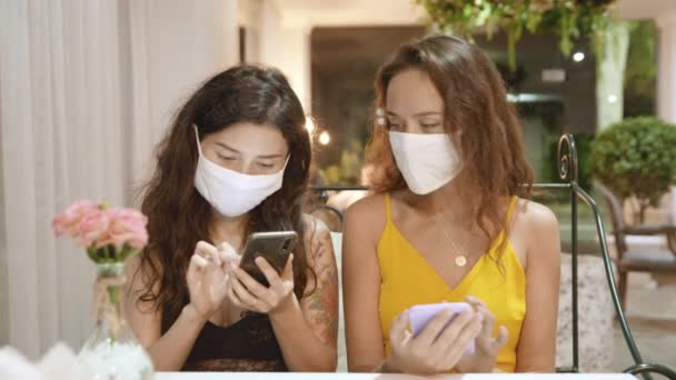 Social distancing. Two women in medical mask sitting at the table at cafe or restaurant and looking at smart phone. New rules after pandemic covid-19. Measures of prevention against virus.