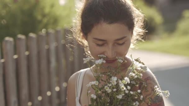 . A nő virágokkal a kezében a szabadban tölti az idejét nyáron vagy tavasszal. Portré gyönyörű mosolygós lány tetoválás az úton a faluban lassú mozgásbanNő pihen a természetben nyaralás közben.