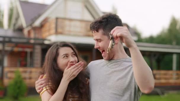 Mladý manželský pár nebo rodina si koupí nový dům. Šťastný muž a žena nebo majitelé třesou klíčem ve vzduchu a objímají se před svým nově zakoupeným domem. Nadšení klienti kupující nemovitosti nebo byt