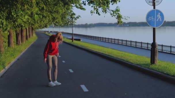 Pěkná blondýnka se zahřívá před běháním nebo cvičením. Dívka protahuje svaly paží a nohou a pak běží podél nábřeží. Atletická žena vede aktivní a zdravý životní styl v karanténě.