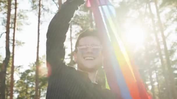 Homosexuál mávající duhovou teplou vlajkou na slunečním světle v krásném letním dni. Šťastný muž se slunečními brýlemi demonstruje svá práva. LGBTQI, Pride Event, LGBT Pride Month, Gay Pride Symbol