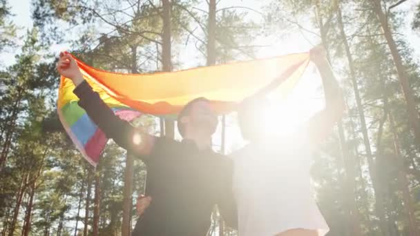 lgbt couple waving rainbow gay flag on sun flare light in beautiful summer day. Happy guys wearing heart sunglasses demonstrate their rights. LGBTQI, Pride Event, LGBT Pride Month, Gay Pride Symbol