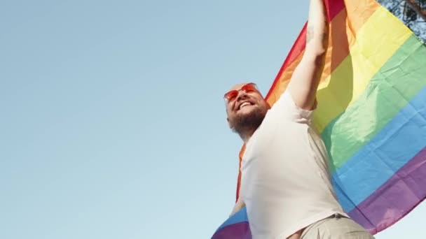 Homosexual man holding rainbow gay flag while parade on background of blue sky. Happy guy wearing heart sunglasses demonstrate his rights. LGBTQI, Pride Event, LGBT Pride Month, Gay Pride Symbol