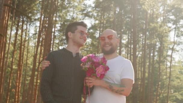 Meleg esküvői koncepció. Két férfi virágcsokorral, gyűrűvel az ujján mosollyal és öleléssel. Egy homokos pár portréja, akik boldogok együtt. Kapcsolati célok. LMBTQI, Pride Event, LMBT Pride Hónap, Meleg Büszkeség Szimbólum