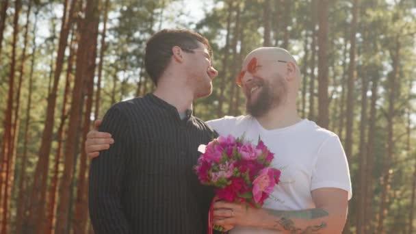 Két férfi virágcsokorral, gyűrűvel az ujján mosollyal és öleléssel. Meleg esküvői koncepció. Egy homokos pár portréja, akik boldogok együtt. Kapcsolati célok. LMBTQI, Pride Event, LMBT Pride Hónap, Meleg Büszkeség Szimbólum