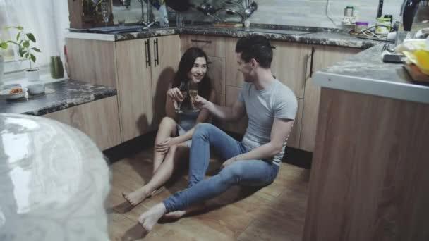 Liebevolles junges Familienpaar sitzt auf dem Boden der gemütlichen Küche und feiert Jubiläum mit Champagner. Interrassische Liebhaber reden miteinander und lächeln. Konzept des ganz normalen Glücks.