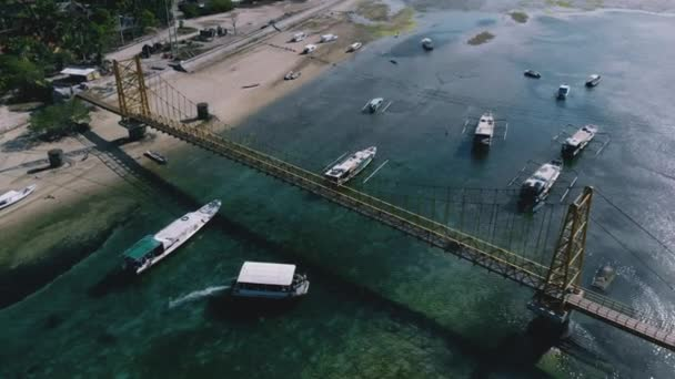 Amazing background of trees, sand coast and clear water. Drone shot along road bridge in magnifficent tropical island. Beautiful view of industry meeting nature. Concept of travel, paradise, sunshine.