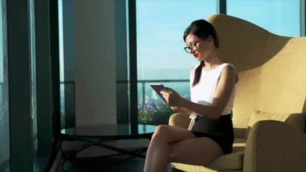 Portrait of pretty businesswoman surfing internet on smartphone and smiling while sitting in lounge zone of modern office or coworking space. Woman in formal wear relax in rest room in business center